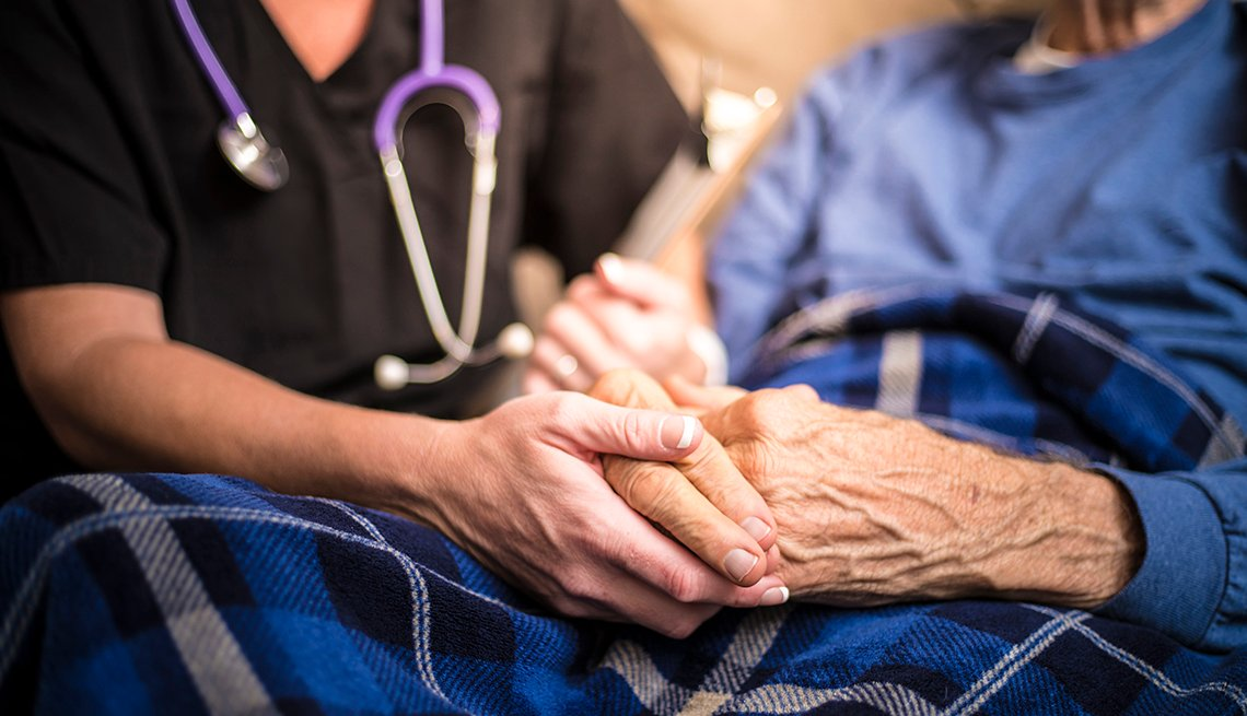 Close up of a hospice nurse holding the hands of one of her patients