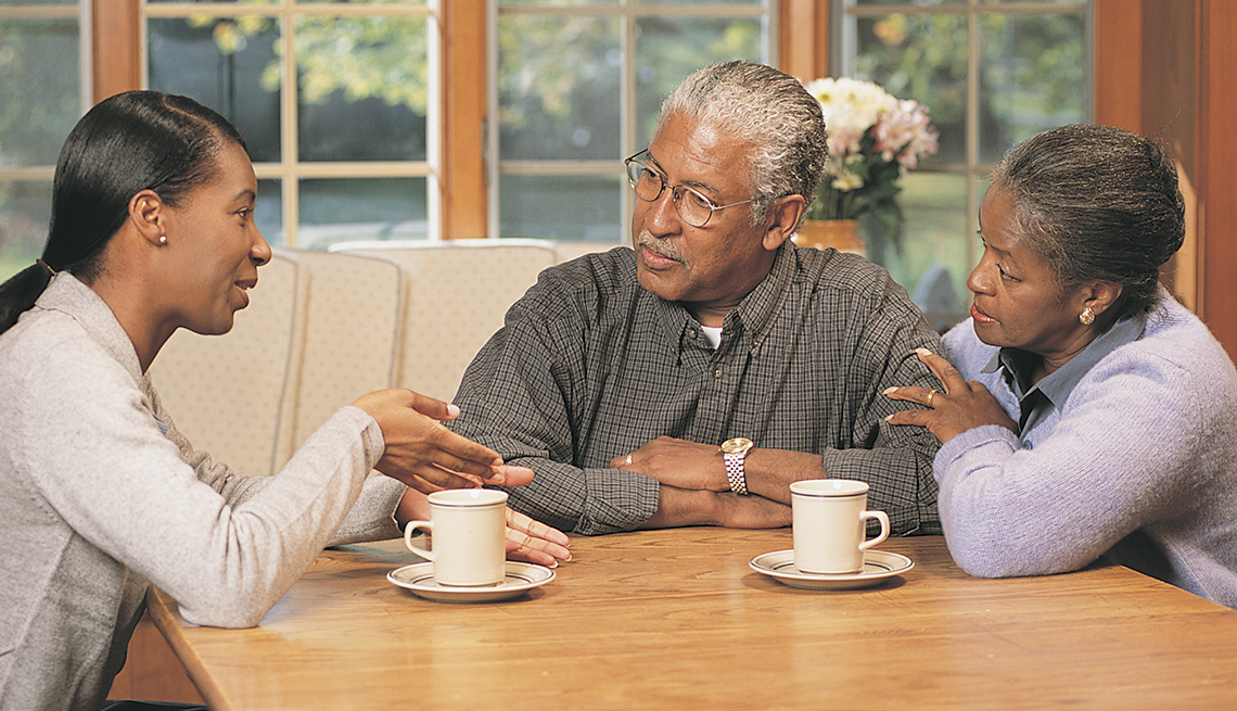 A woman speaks to her parents at a table in their home