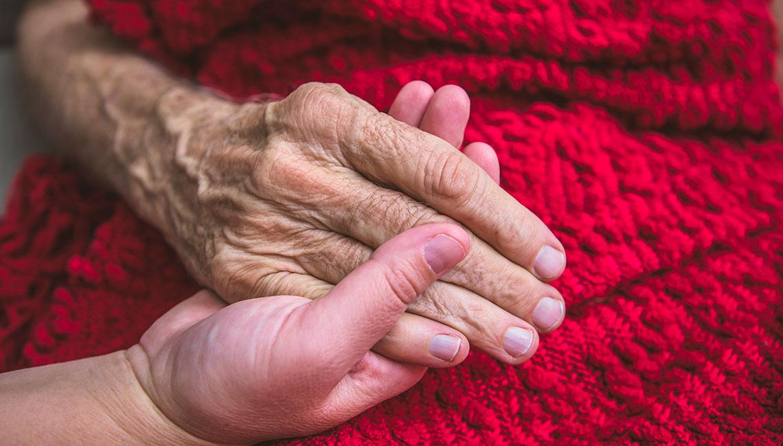 Persona joven sostiene la mano de un anciano