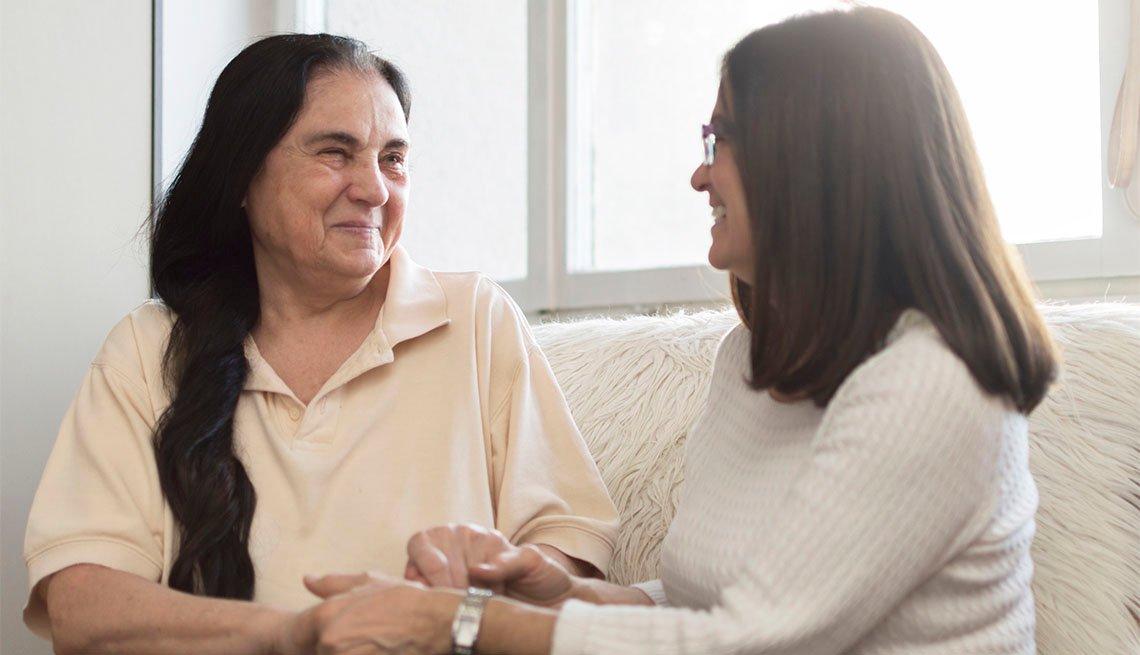 Dos mujeres conversan sentadas en un sofá