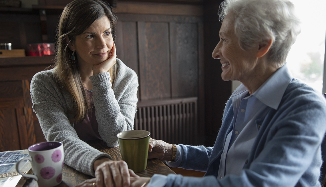 Adult woman having coffee with her mother at the kitchen table