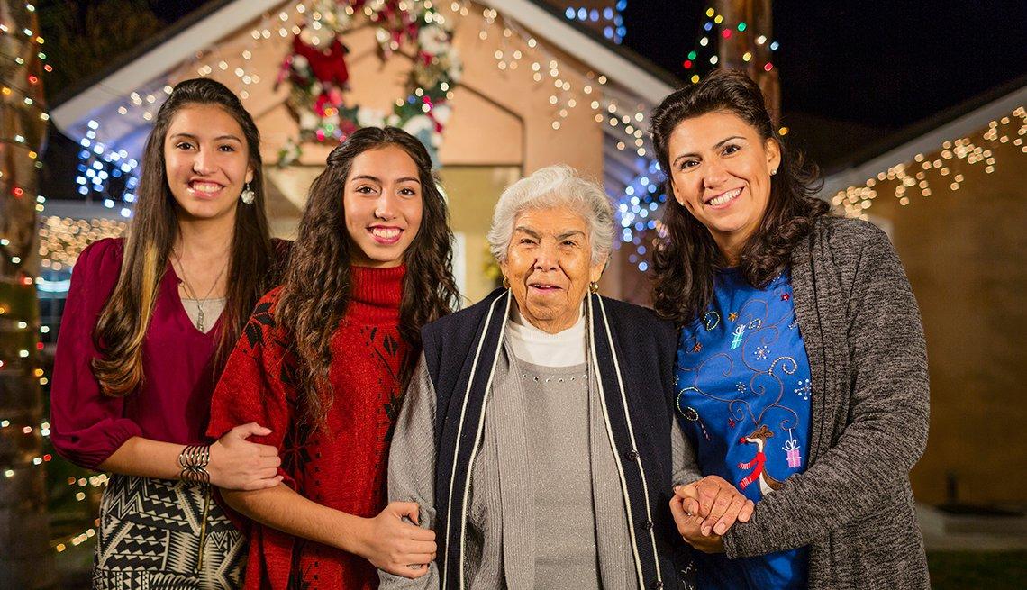 Tres generaciones de mujeres paradas frente a su casa decorada de Navidad