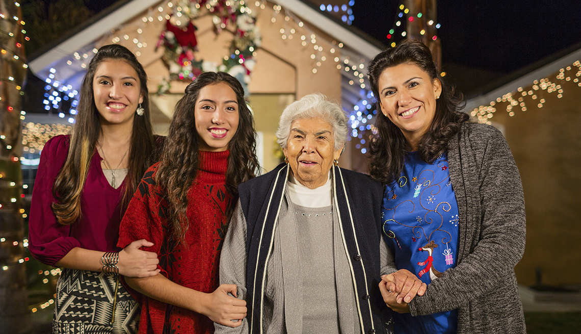 Three generations of Hispanic women smiling outside of a house decorated with string lights