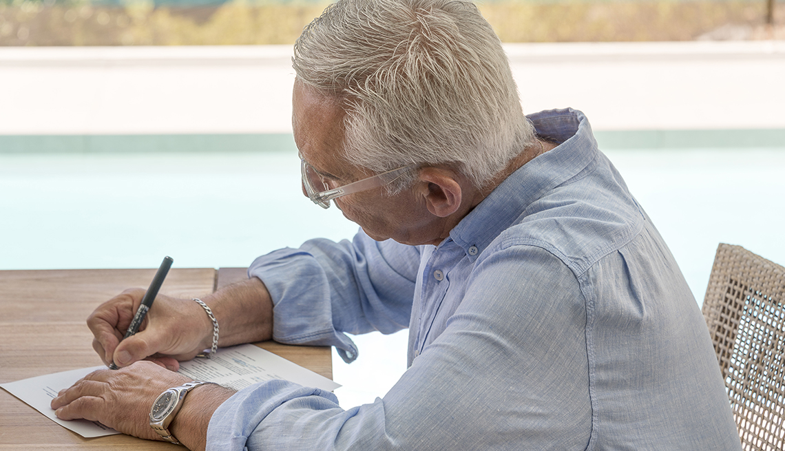 older man filling out paperwork at table