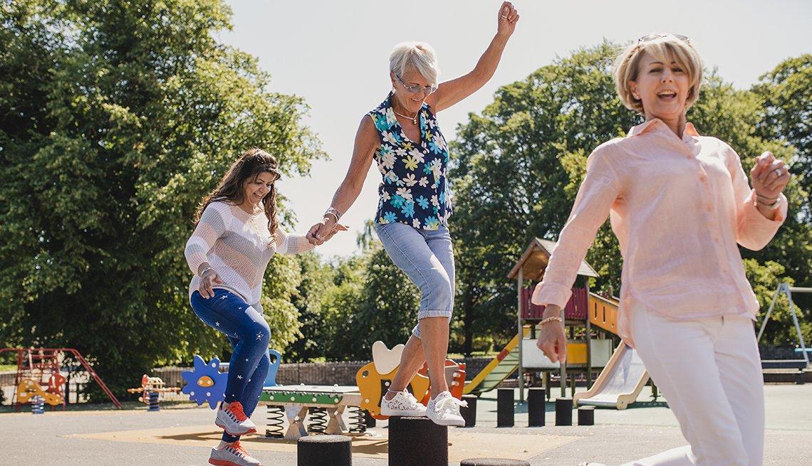 senior women balance on playground stepping stones