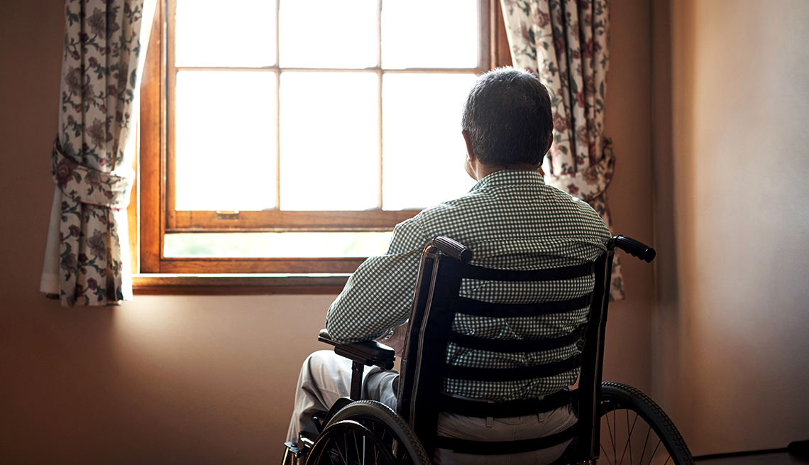 Rearview shot of a lonely senior man in an assisted living facility looking out the window while sitting in his wheelchair
