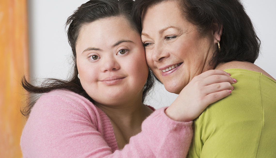 A young woman with down syndrome hugging her mother