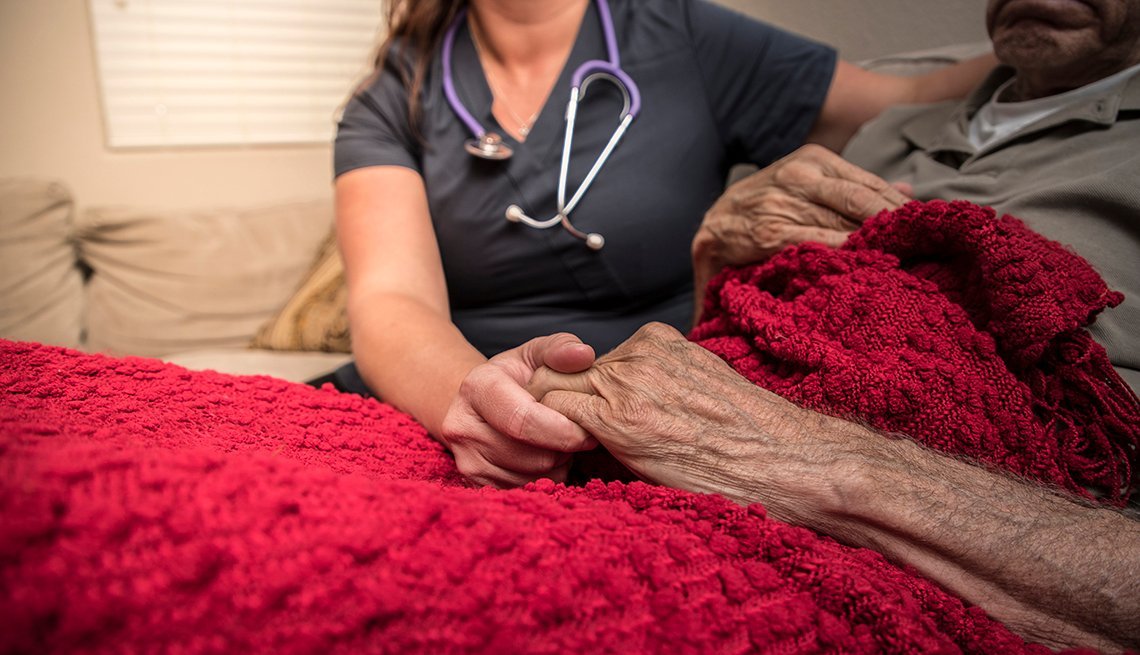 A doctor providing palliative care to a man at home. Close up of them holding hands while the man lays down.