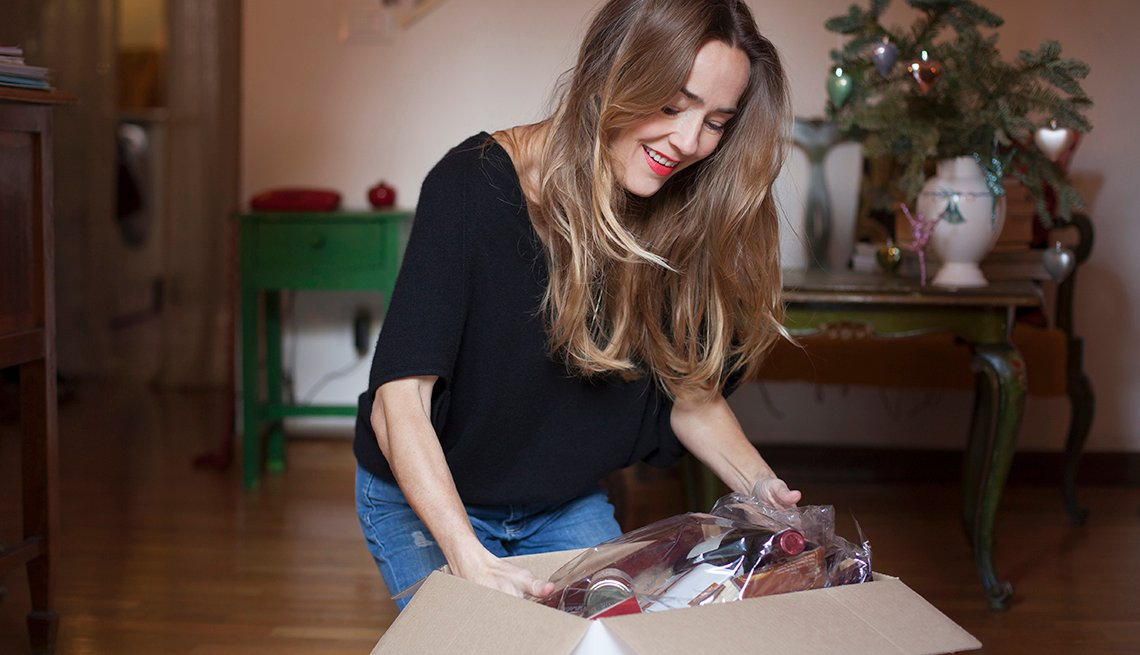 Woman opening a box containing a gift basket