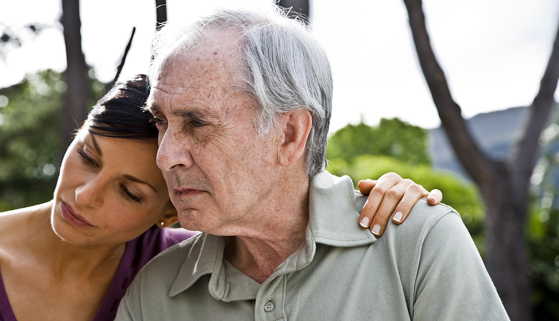 Woman with her arm around her father, both looking sad