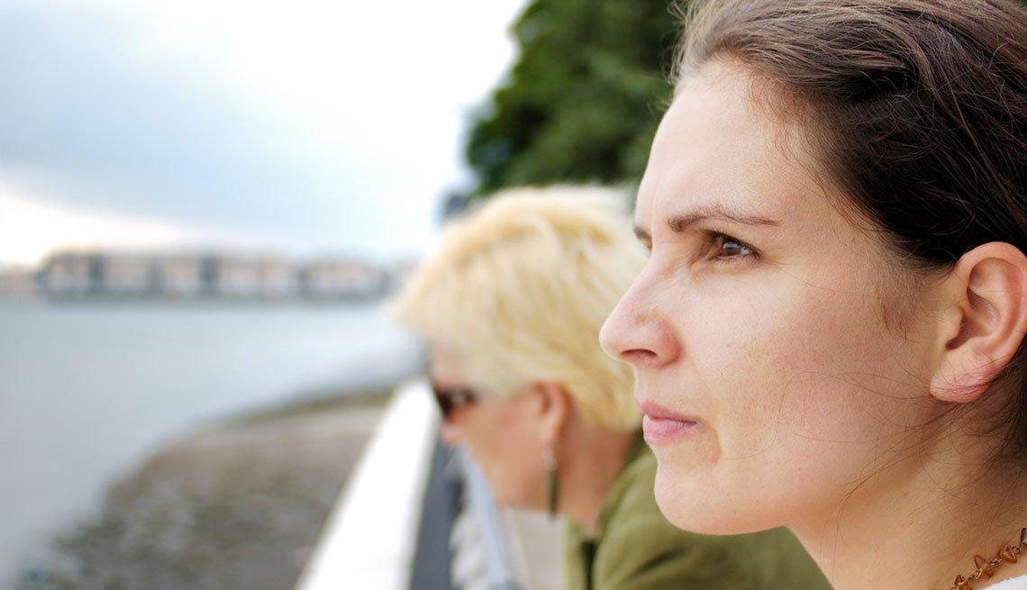 Mujer joven y mujer mayor al fondo observan un paisaje