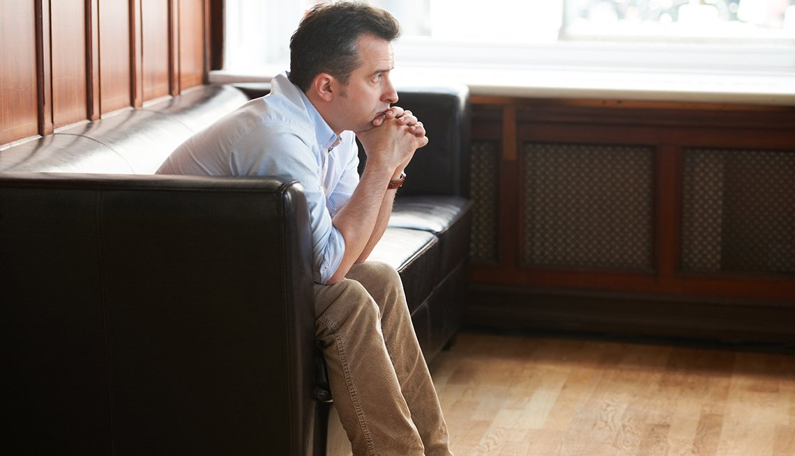 A man sitting on a sofa, looking sadly into the distance