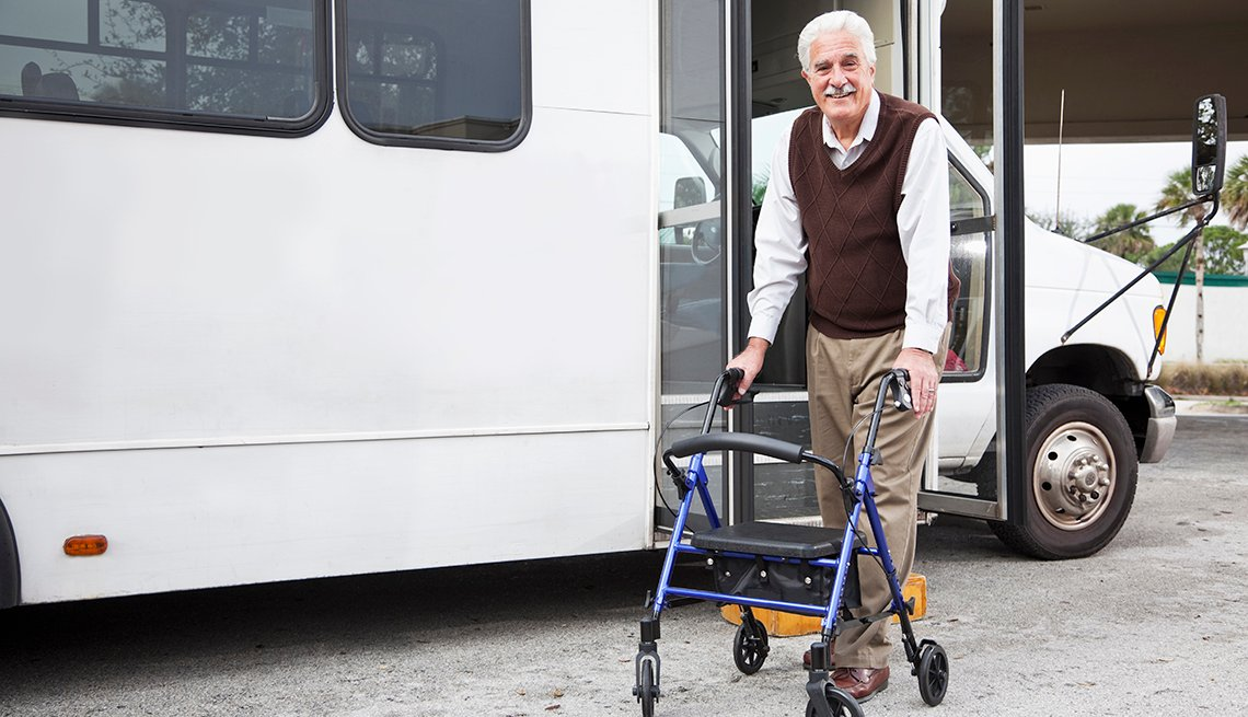 Man using a walker getting into a public transportation van