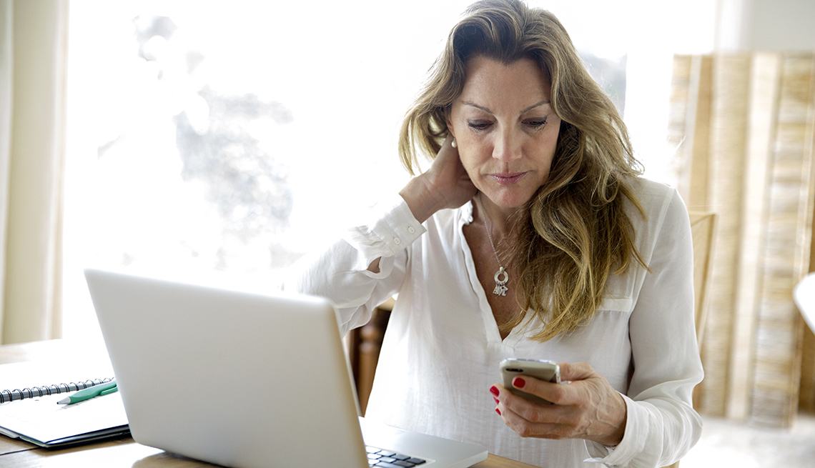 Woman at work with a laptop in front of her, being distracted by a message from home on her mobile phone