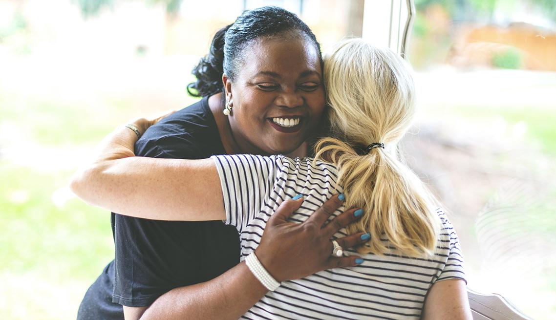 Dos mujeres se abrazan en un saludo