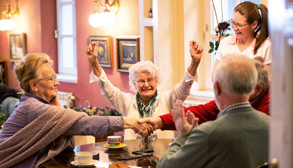Residents of a group care home playing a game together while a female aide looks on