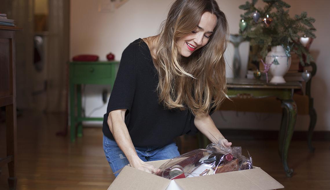 Una mujer abre una caja de regalo