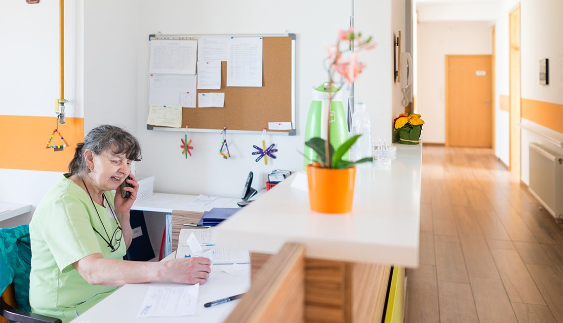 Nurse sitting at desk and answering phone