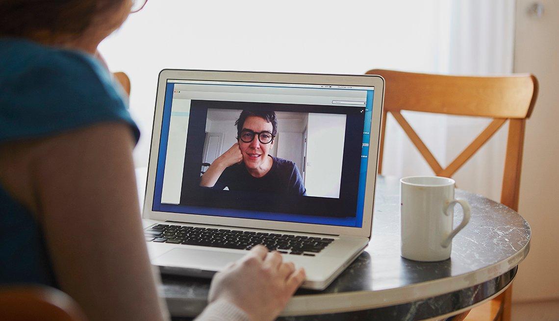 Una mujer conversa con un familiar a través de una videollamada
