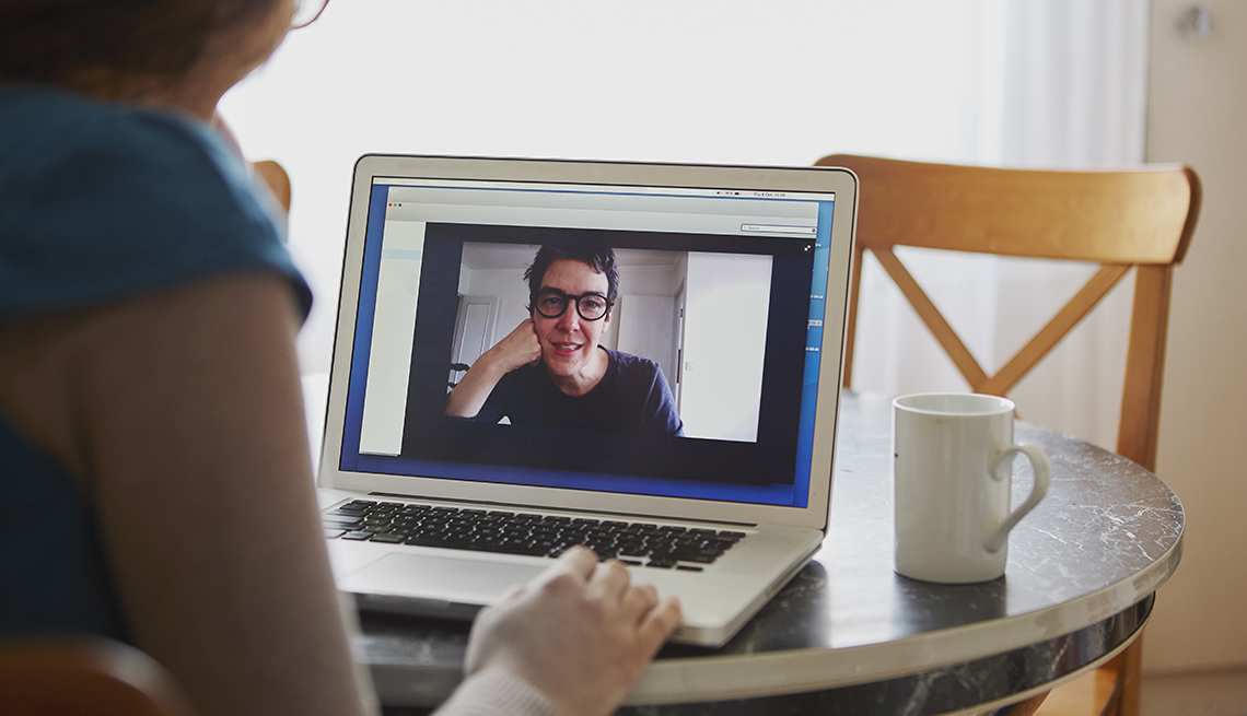 A woman sitting at table using a laptop on a video call with another woman