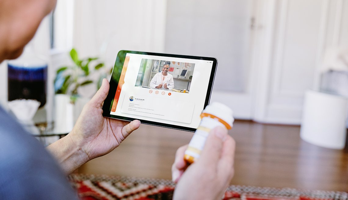 Male family caregiver holding a prescription bottle and video chatting with a doctor on a tablet during a telehealth call