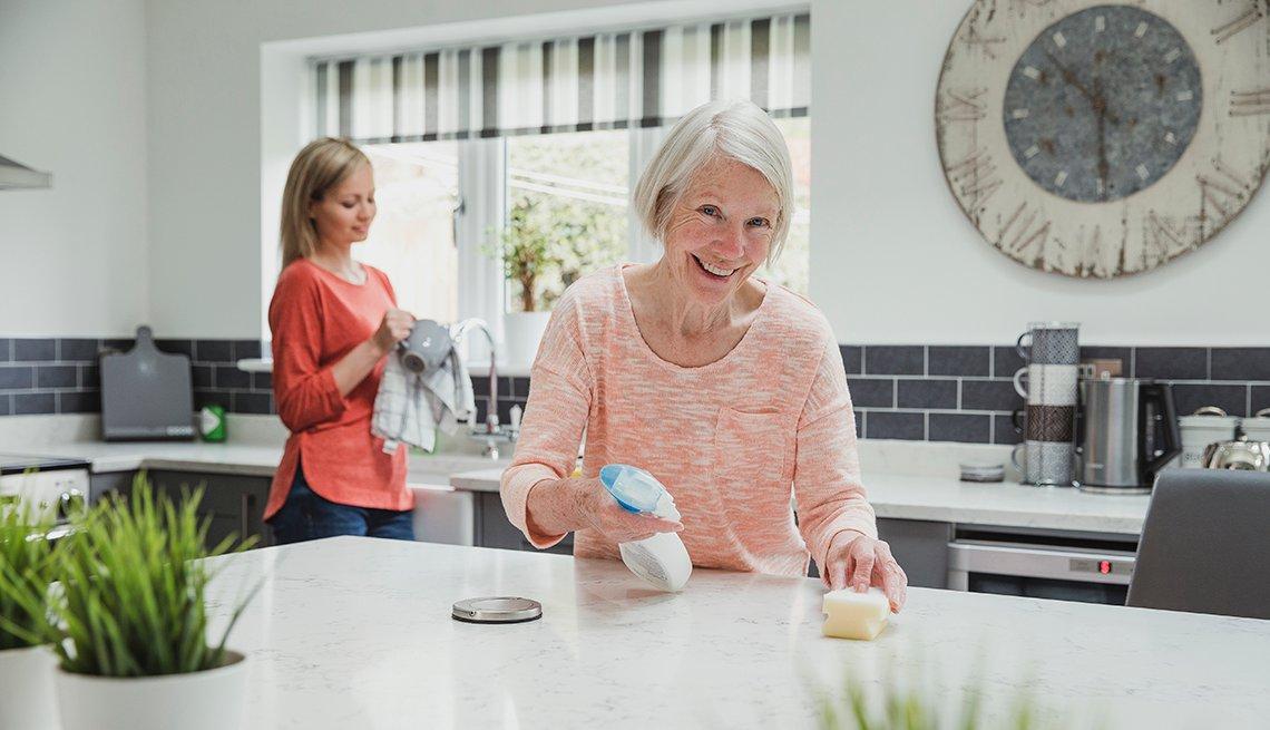 Una mujer y su hija limpian y desifectan su cocina
