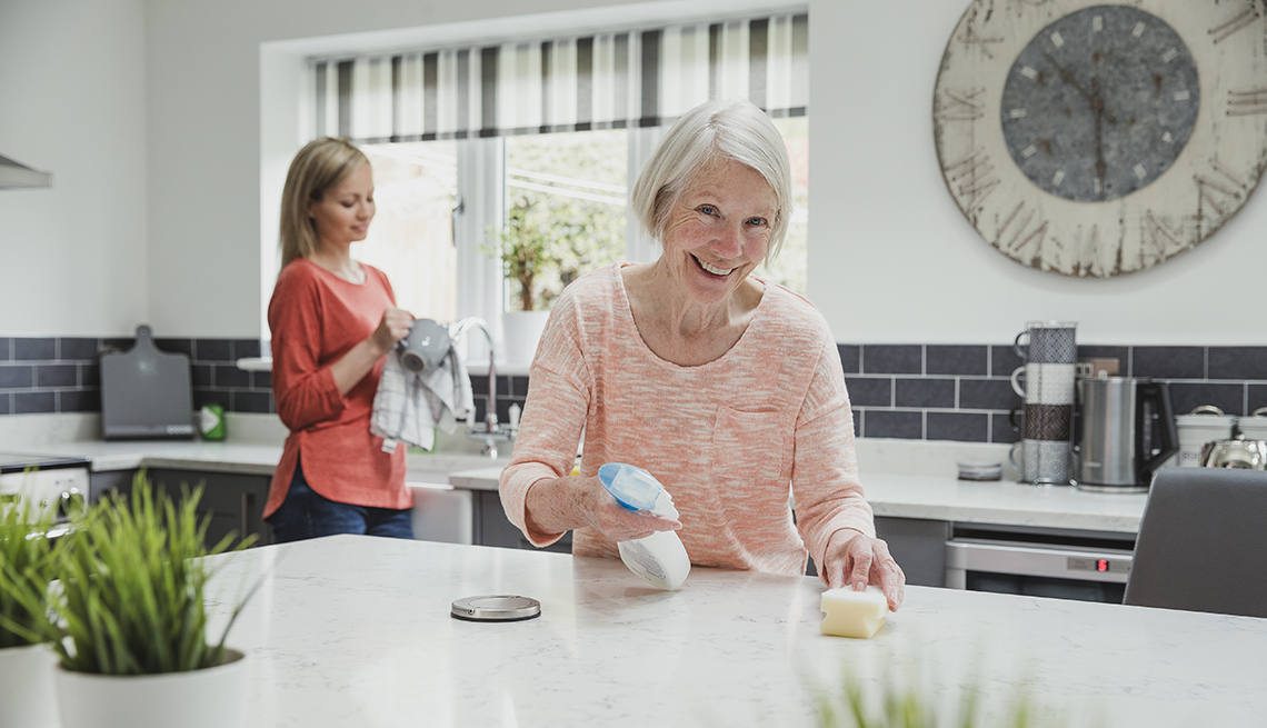Woman and her daughter cleaning surfaces to disinfect against the coronavirus