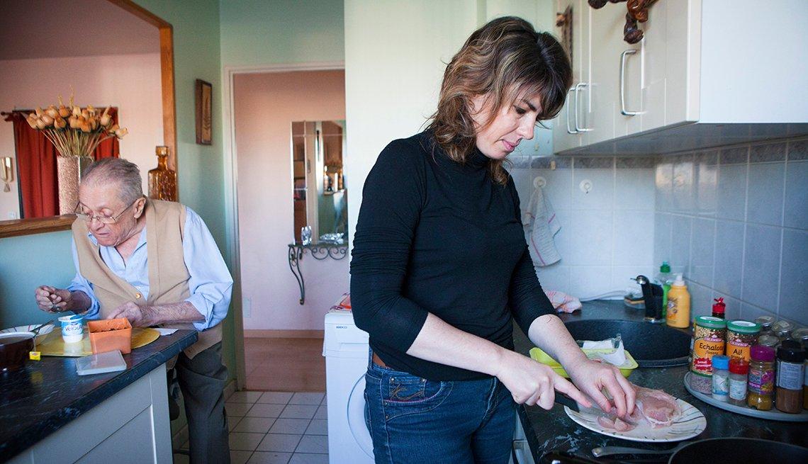 Una mujer prepara alimentos para su padre mientras el come un yogur