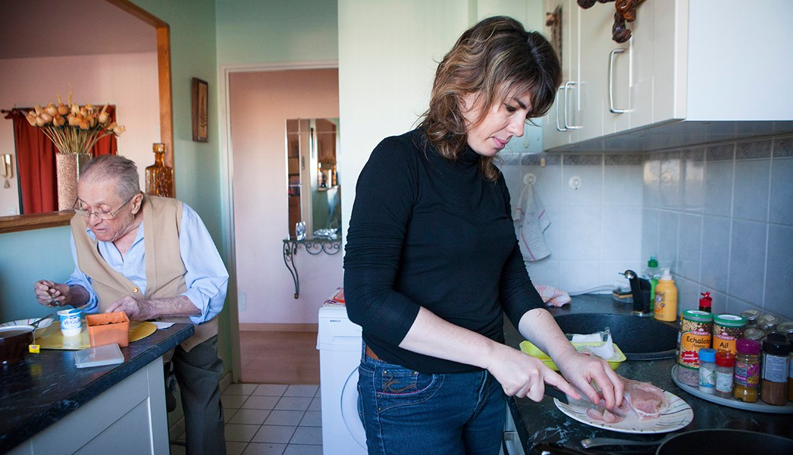 A woman preparing a meal for her father as he eats a yogurt snack in the background