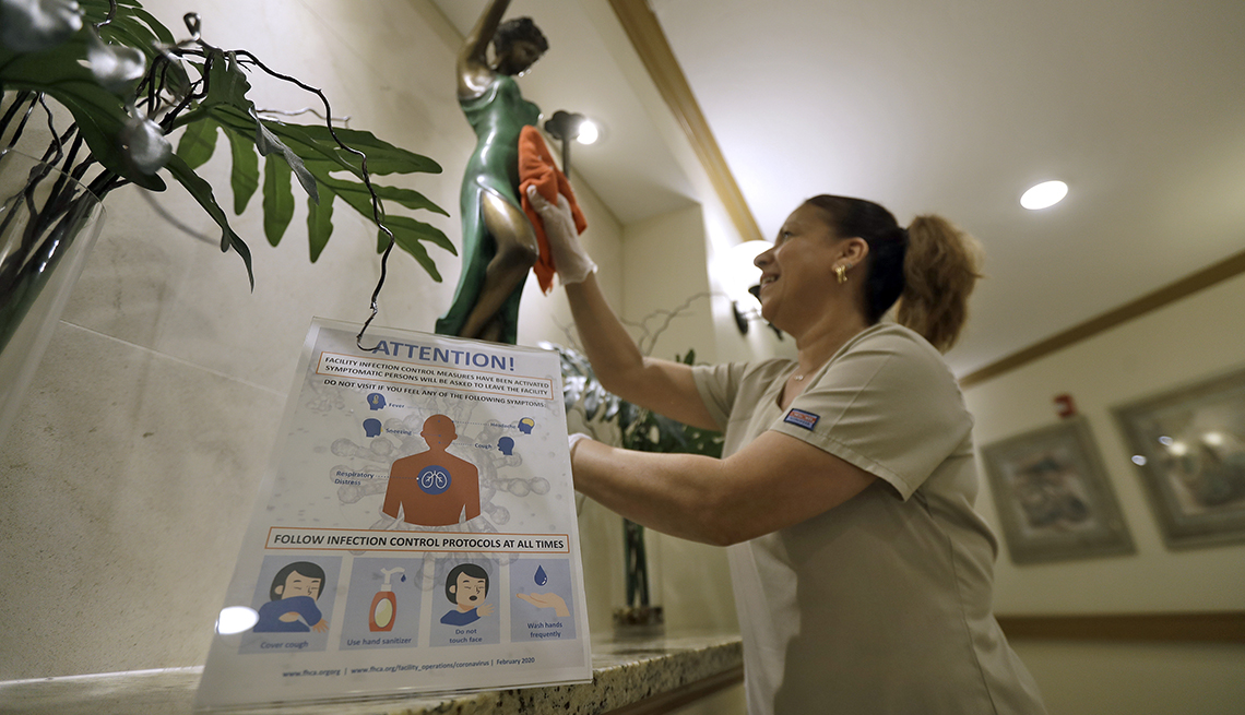 A female Environmental Services member cleans behind an infection control warning poster at a rehabilitation center