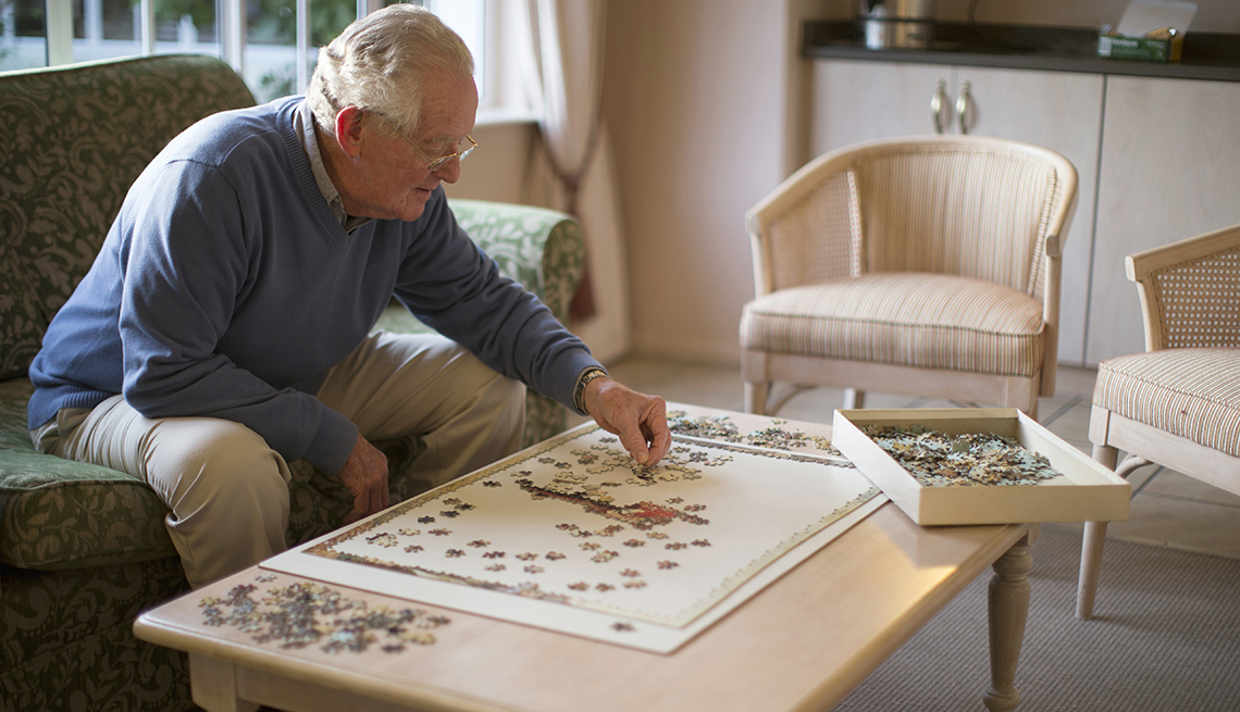 Man in a nursing home staying busy by doing a puzzle his family sent him
