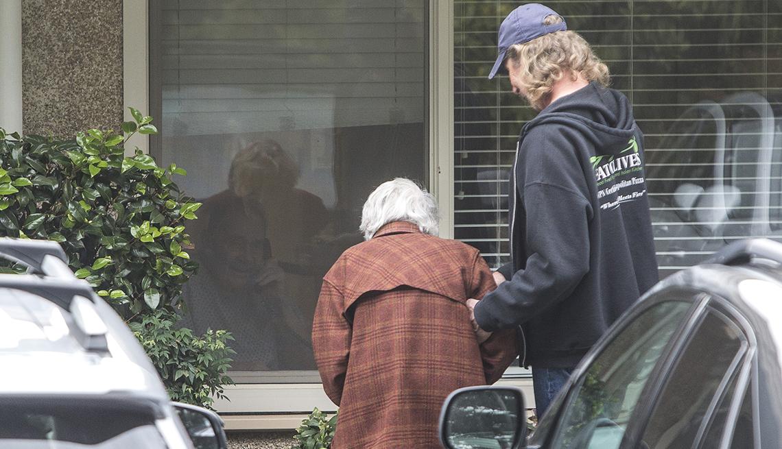 Un hombre ayuda a su mamá a ver a su papá a través de una ventana