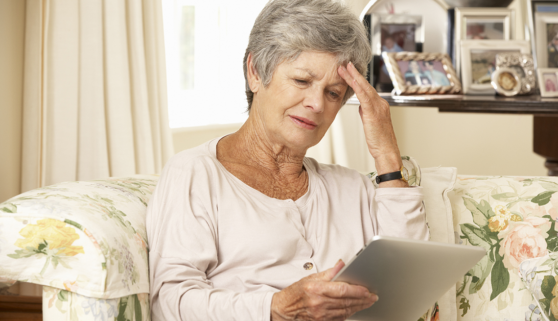 Woman in a nursing home holding a tablet and looking frustrated