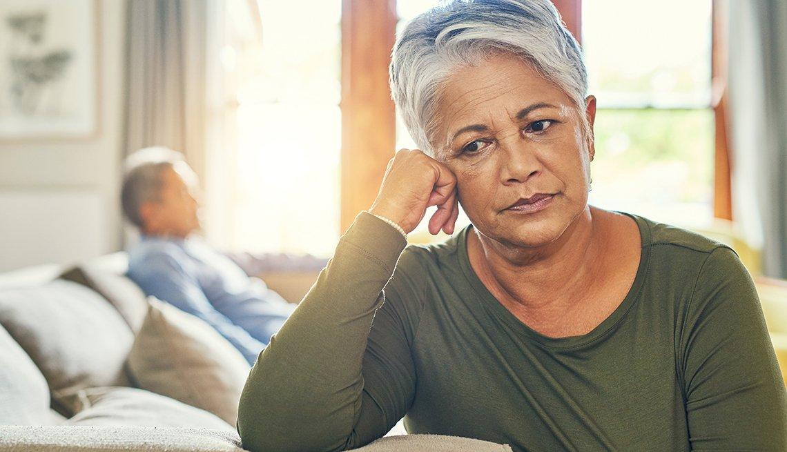 A woman sitting on her couch looking sad as she dreads her upcoming caregiving duties. A blurred image of an older man is in the background