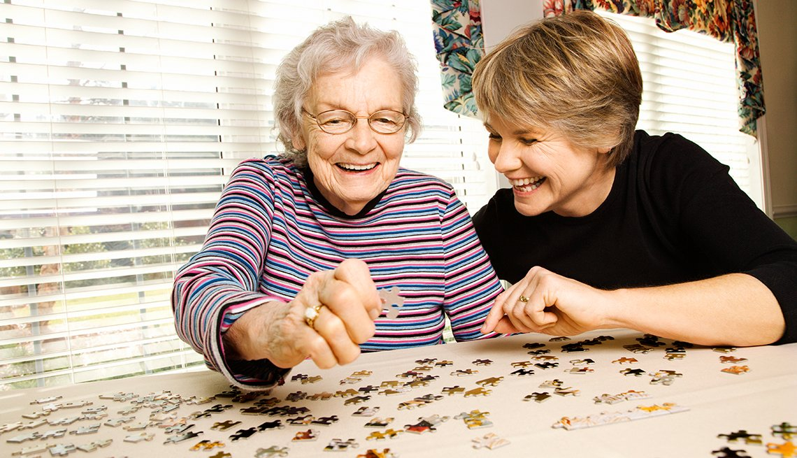 Adult woman doing a puzzle with her mother