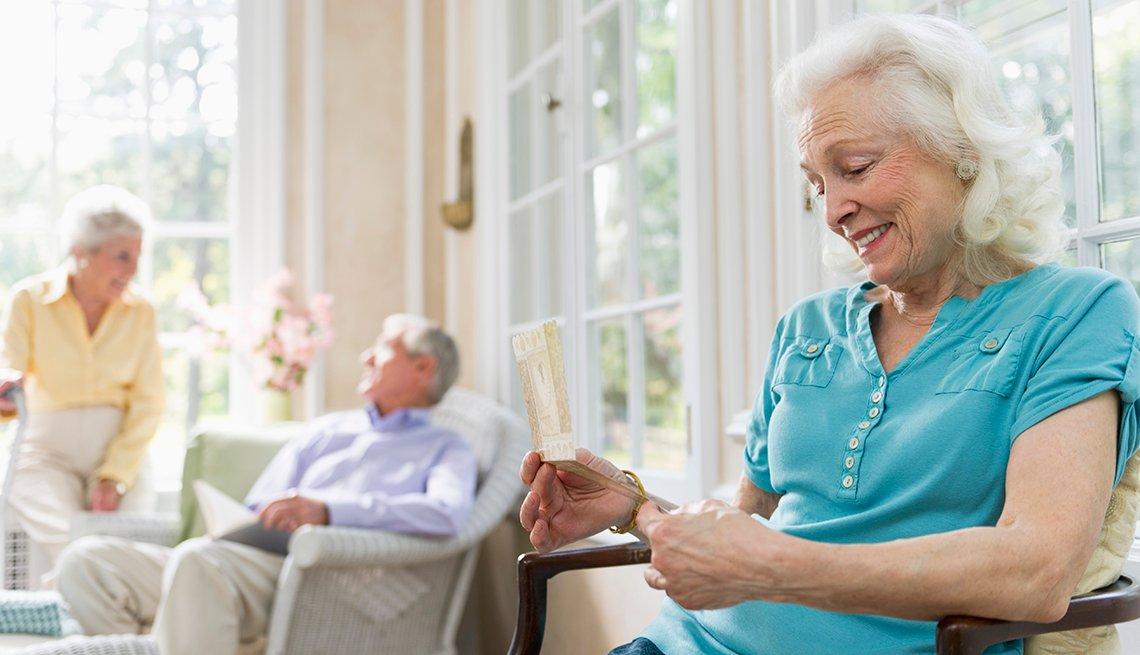 Una mujer en un hogar de ancianos lee una postal
