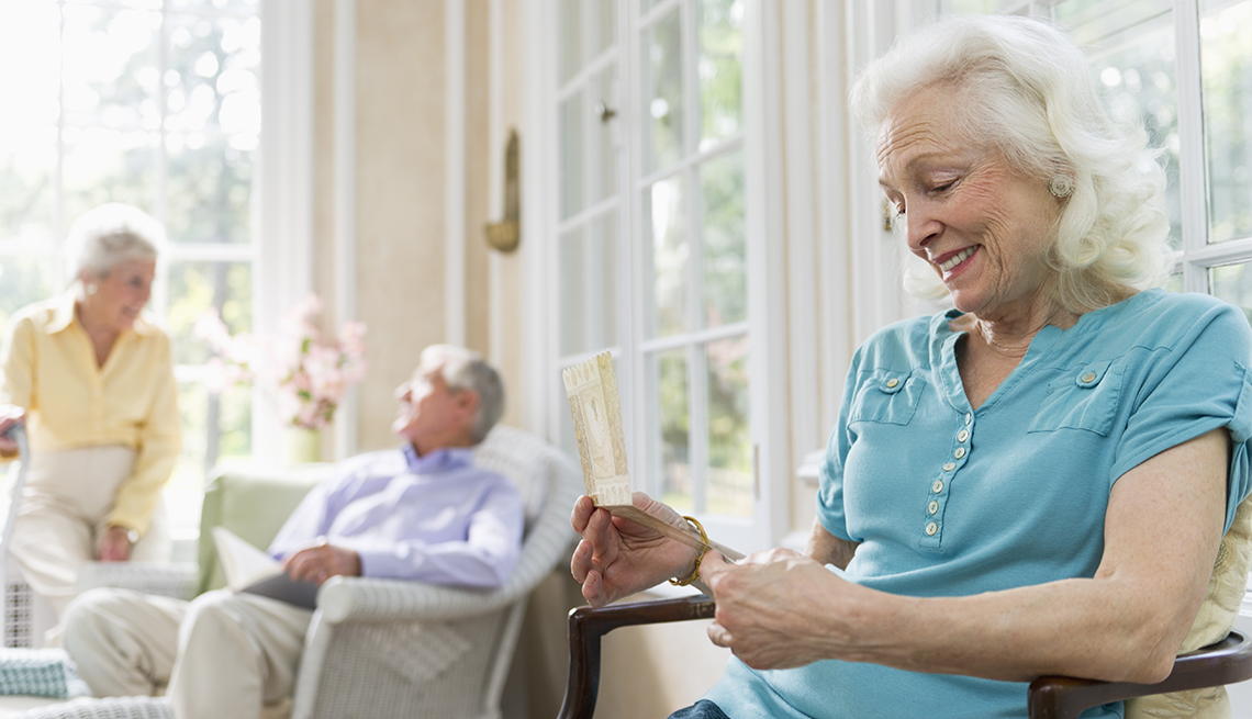 A woman in a nursing home looking at a card she received from a family member