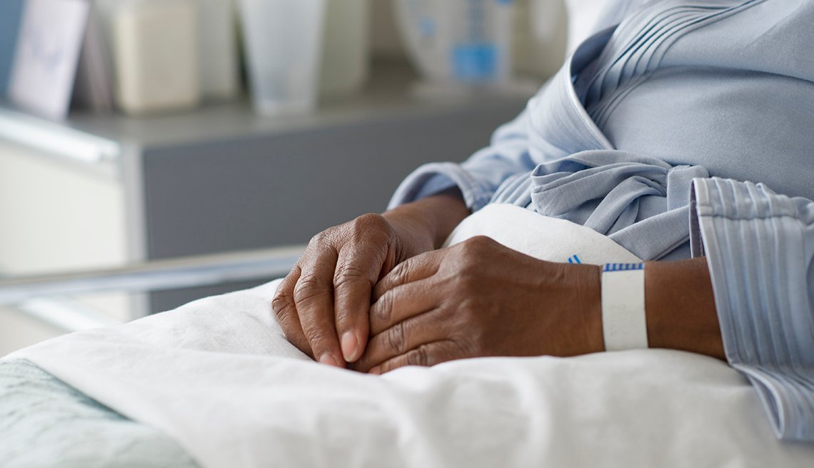 Close up of the hands of a woman laying in a nursing home hospital bed