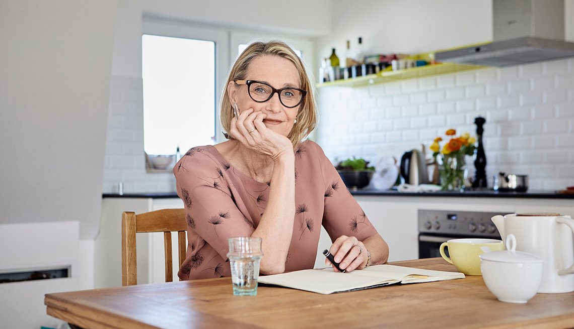 Woman sitting at her kitchen table writing in a journal