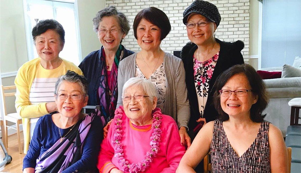 Seven women pose in front of an 80th birthday cake