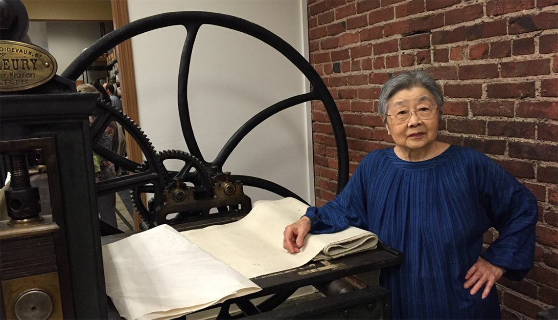 Jean Kubota Cassill standing next to an historic French printing press