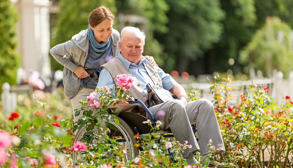 Una mujer lleva a un hombre en su silla de ruedas por un jardín