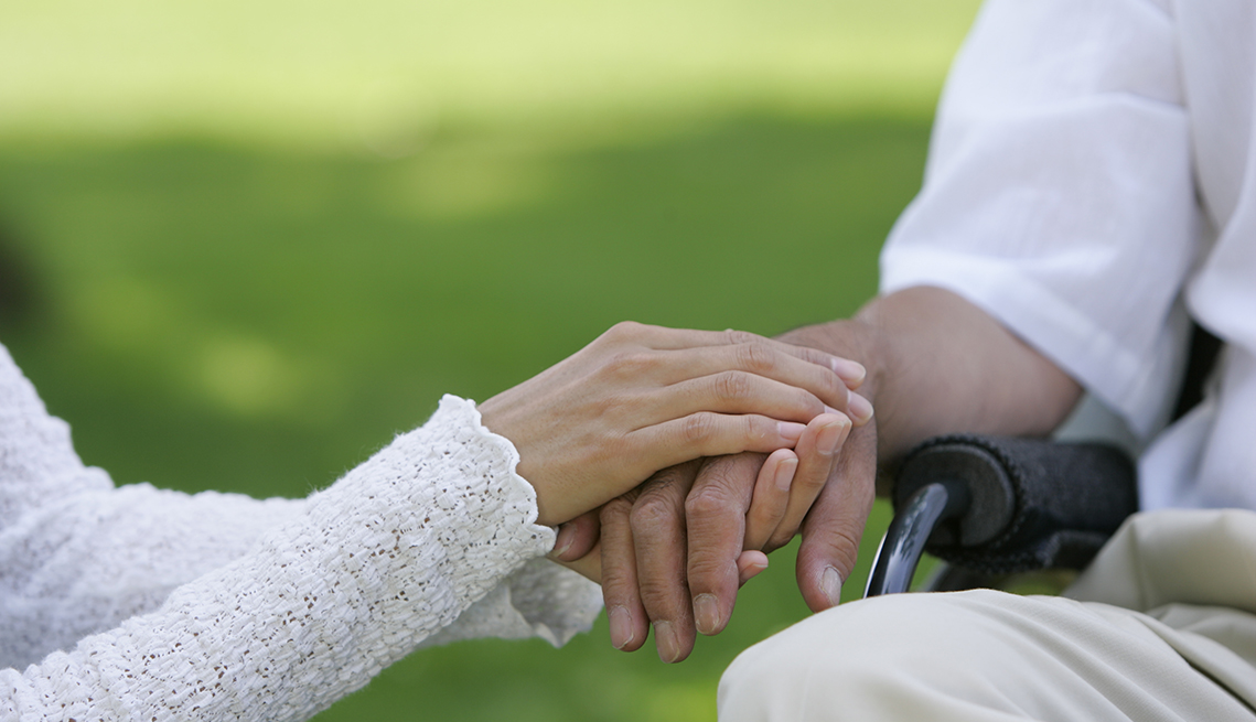 Close up of a woman holding the hand of a man sitting in a wheelchair