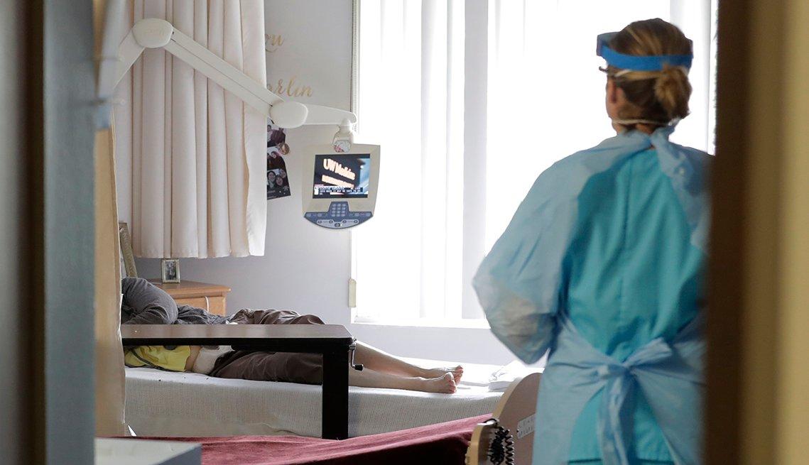 Personal médico, debidamente protegido entra a una habitación de hospital