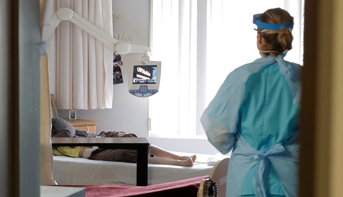 A medical worker wearing personal protective gear stands in the doorway of a nursing home room as a patient lays in bed inside