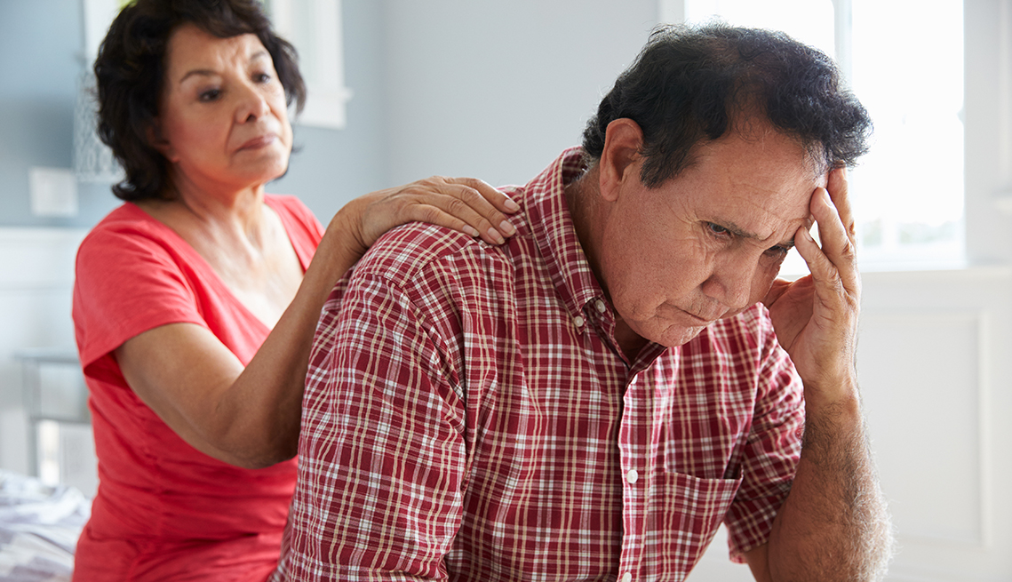 Woman with her hand on her husband's shoulder, comforting him as he grieves