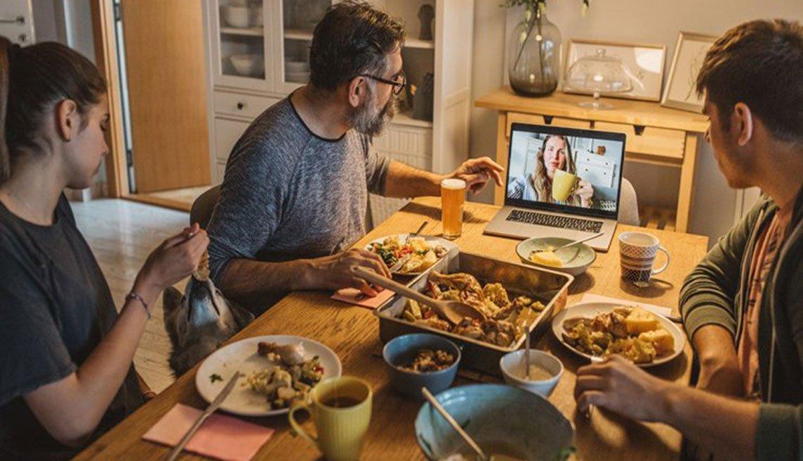 Familia sentada a la mesa cenando mientras conversan con una persona a través de una videollamada