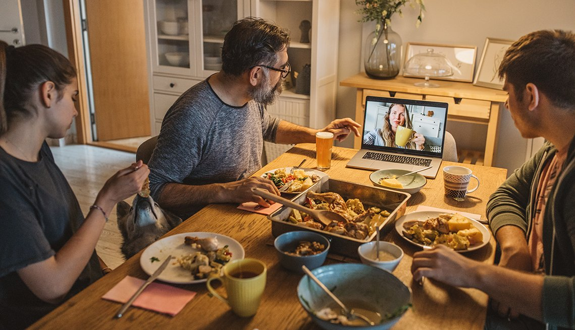 Dad and two teenage children having dinner while video chatting with a relative