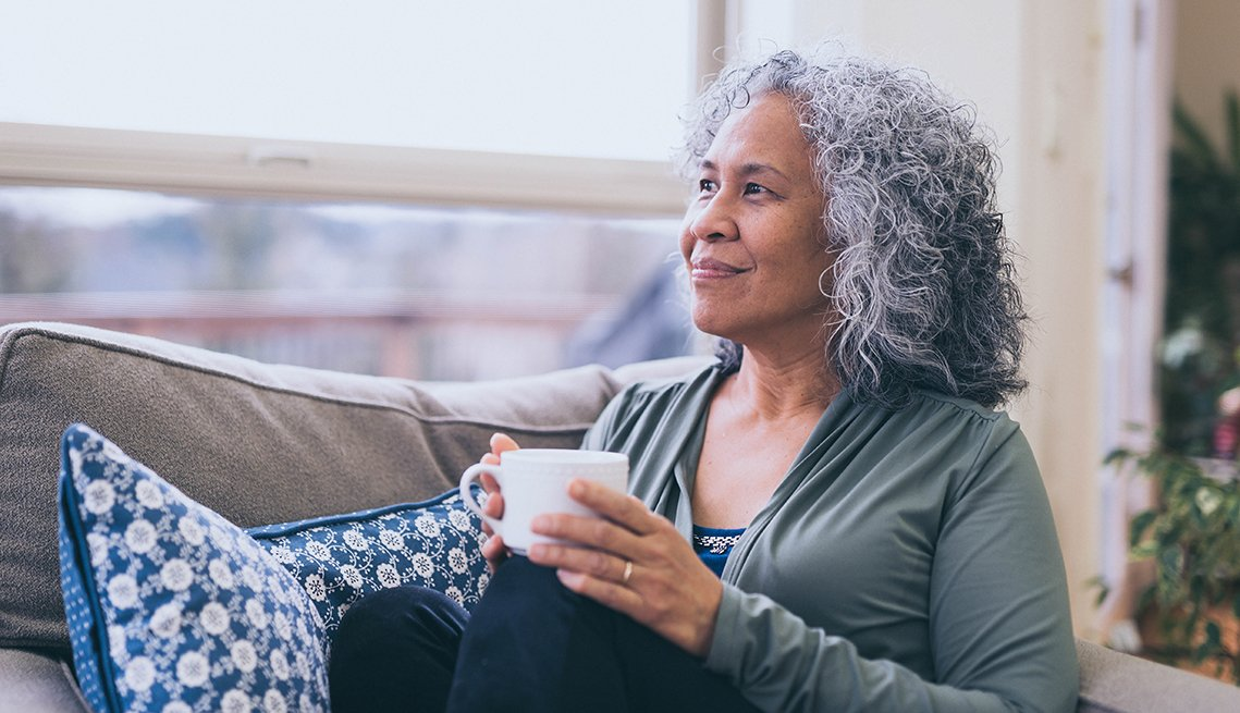 Woman sitting on the couch with a cup of coffee looking calmly out the window