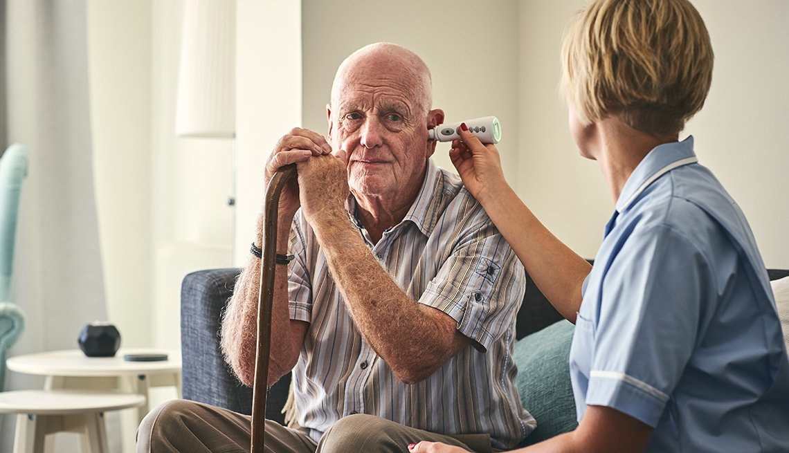 An in-home caregiving aide taking her patients temperature to screen him for the coronavirus